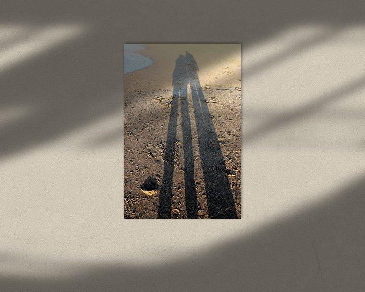 Sfeerimpressie: Lange schaduw van een koppel op het strand van Anna van Leeuwen