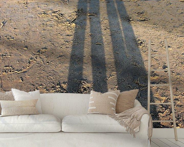 Sfeerimpressie behang: Lange schaduw van een koppel op het strand van Anna van Leeuwen
