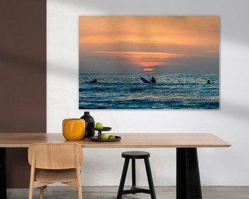 Surfers bewonderen de zonsondergang in het water bij Terschelling