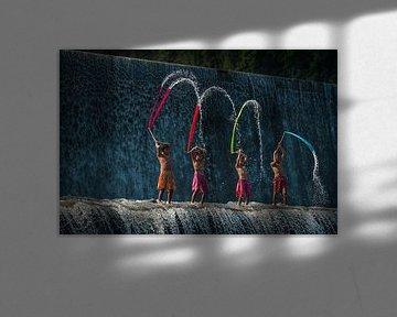 Balinese jongens spelen met gekleurde lappen stof op de Tukad Unda waterdam in Bali van Anges van der Logt