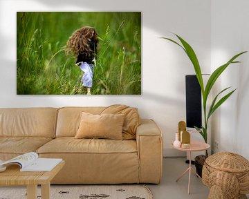 Jonge  vrouw met lang bruin haar in het hoge gras. van Margreet van Tricht