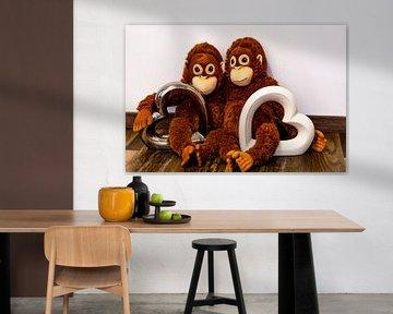 Zwei Stofftier Affen sitzen Arm in Arm und haben zwei Herzen in der Hand von Tom Voelz