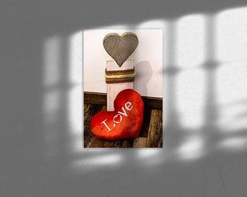 Un coeur en tissu rouge devant un coeur en bois sur Tom Voelz