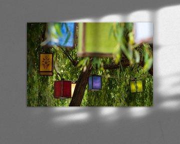Lantaarns in verschillende kleuren onder de boom in Hobbiton, Nieuw-Zeeland van Paul van Putten