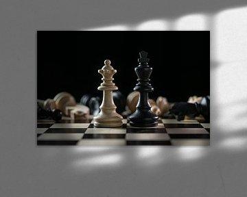 Schaakstukken koningin en koning voor een van de gevallen schaakstukken na een slagveld op een schaa van Maren Winter