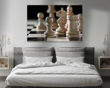 Witte houten schaakstukken met focus op de ridder op een schaakbord tegen een zwarte achtergrond, ko van Maren Winter
