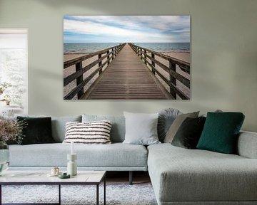 Houten pier leidt recht over het strand en de zee naar de horizon, concept voor de weg naar een onze van Maren Winter
