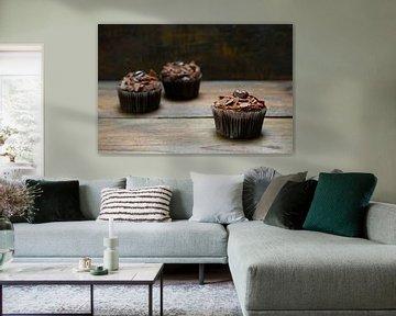 drie chocoladecupcakes met cacaobotercrème op donker hout, een is in focus, kopieerruimte, smalle sc van Maren Winter