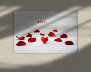"""cœur de verre rouge entre des pétales de rose sur un fond de bois gris clair, texte """"Je t'aime&"""
