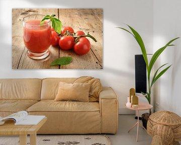 vers biologisch tomatensap in een drinkglas met peper en basilicumgarnituur op een rustieke houten p van Maren Winter