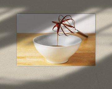 Bruine suikersiroop stroomt uit een draadklopper in een witte kom, bakkend thuisconcept, houten tafe van Maren Winter