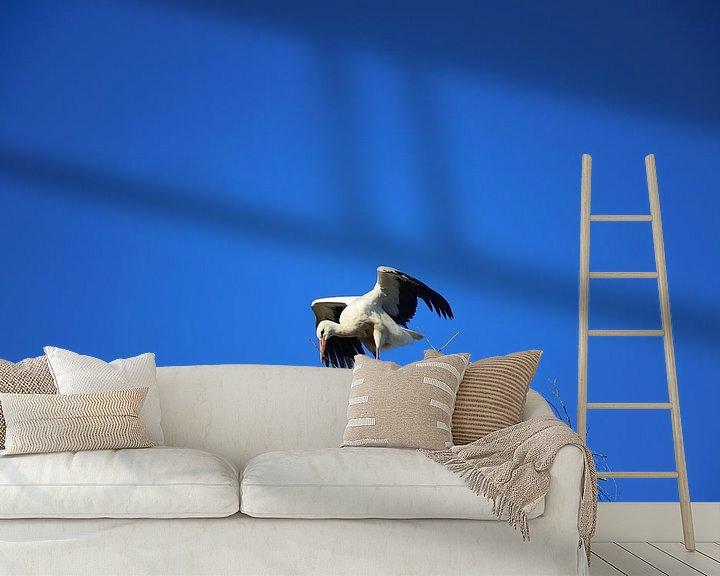 Sfeerimpressie behang: Een ooievaar spreidt zijn vleugels in het ooievaarsnest... van Ulrike Leone