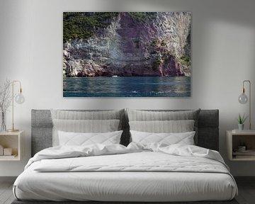Kleine zeilboot in een baai voor de rotsachtige kliffen van de middellandse zee, kopieerruimte van Maren Winter
