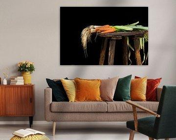 carottes et poireaux biologiques récoltés dans le potager sur un vieux tabouret en bois sur fond noi sur Maren Winter