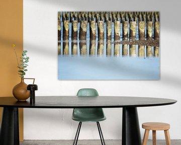 houten kribben in rijen aan zee met reflecties op het wateroppervlak, kustbescherming in de Oostzee, van Maren Winter