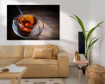 zwarte thee vers gezet in een glazen beker en een lepel op een donkere rustieke houten tafel, dampen van Maren Winter