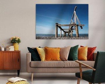 Gebroken houten pier of steiger leidt naar de zee tegen een blauwe hemel, perspectief van onderaf, k van Maren Winter