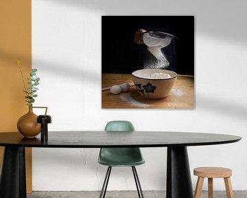 farine tombant d'un tamis dans un bol sur un plan de travail de cuisine en bois lors de la préparati sur Maren Winter