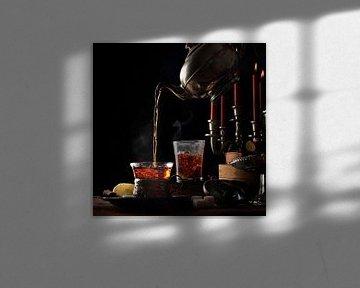 Het gieten van hete dampende thee uit een vintage theepot in glazen kopjes op een rustieke tafel met van Maren Winter