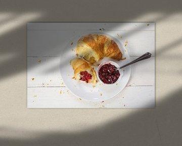 verse croissant met rode cranberryjam voor het ontbijt op een bord op een witte houten tafel, uitzic van Maren Winter