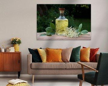 Zelfgemaakte vlierbloesemdrank met suiker en citroen in een glazen fles op een houten tafel in de tu van Maren Winter