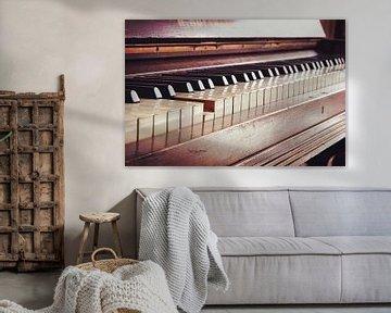 oude vintage pianoklavier, één toets wordt ingedrukt, muziekconcept in warme kleurtonende retrostijl van Maren Winter