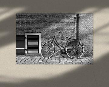 Traditionelles schwarzes Fahrrad gegen eine Ziegelmauer von Tony Vingerhoets