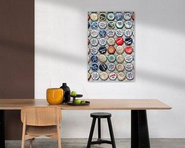 Bonte verzameling beer bottle caps geplakt op een muur van Tony Vingerhoets