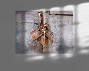 Rusty Vorhängeschloss auf einem alten grau lackierten Metall-Gate von Tony Vingerhoets