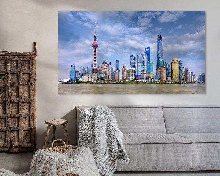 Sfeerimpressie: De horizon van Shanghai met hoge wolkenkrabbers tegen een blauwe hemel van Tony Vingerhoets