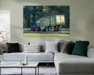 Groene tractor die gemaaid gras opraapt met een groene opraapwagen in de zomer in Nederland van Tonko Oosterink