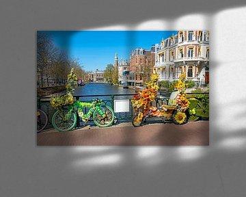 Geschmückte Fahrräder mit Blumen auf dem Kanal in Amsterdam von Nisangha Masselink