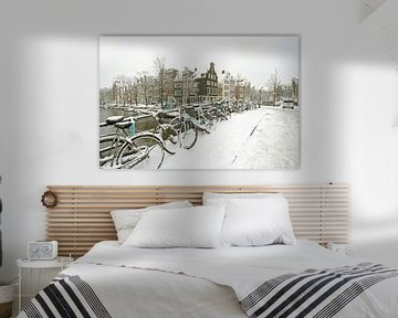 Verschneite Fahrräder auf den Grachten in Amsterdam im Winter von Nisangha Masselink