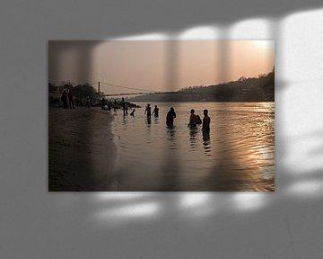 Mensen nemen een bad in de heilige rivier de Ganges in India bij zonsondergang van Nisangha Masselink