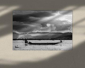 Schwarz-Weiß-Foto eines Fischers, der bei Sonnenuntergang am Inle-See in Myanmar seine Netze aufhebt von Twan Bankers