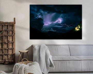 Blitz klärt den Himmel in der Nähe einer Burg in den Bergen von Menno van der Haven