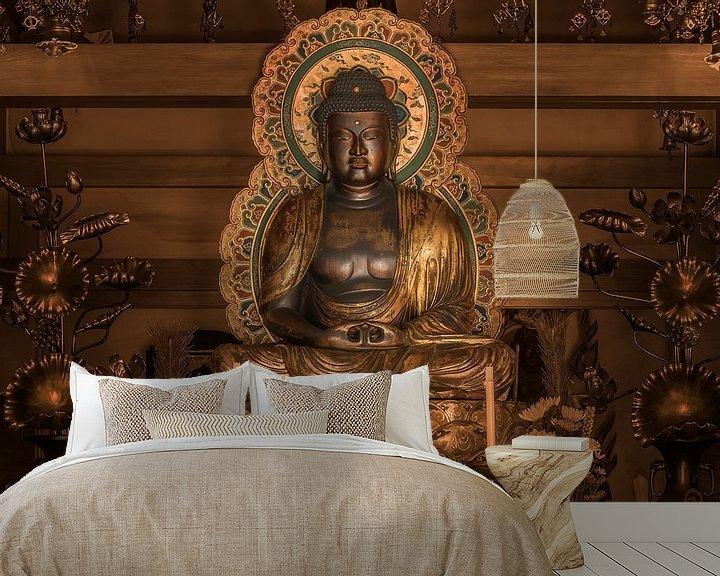Sfeerimpressie behang: Gouden standbeeld van de Japanse Boeddha Shakyamuni omgeven door lotusbloemen. van Kuremo Kuremo