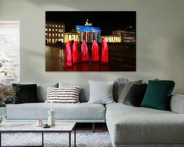 Cinq sculptures rouges devant la porte de Brandebourg illuminée