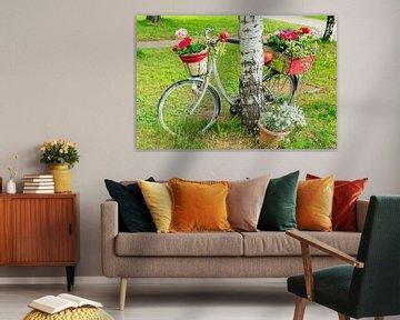 Ein mit Blumen dekoriertes Fahrrad lehnt an einem Baum.