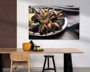 Vers gekookte blauwe mosselen met citroen- en peterseliegarnituur op een bord, donkere servet en lei van Maren Winter