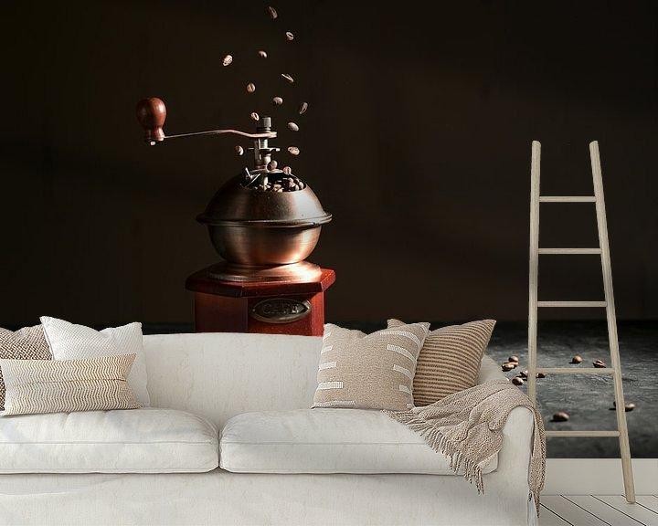 Sfeerimpressie behang: Houten vintage koffiemolen op een leisteenplaat, vallende en liggende gebrande bonen tegen een donke van Maren Winter