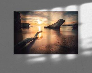 Zonsondergang aan de kust van Griekenland met strand en stenen en tak van Fotos by Jan Wehnert