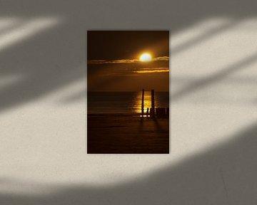 Golfbrekers in de zonsondergang.