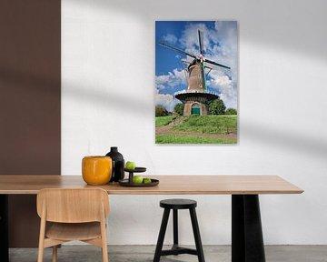 Traditionele Nederlandse windmolen op een dijk tegen een zonnige blauwe hemel van Tony Vingerhoets