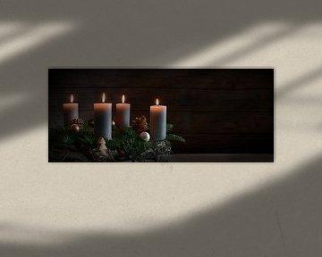 Vier brandende kaarsen op een adventskrans van dennentakken met kerstversiering tegen een donkere ru van Maren Winter