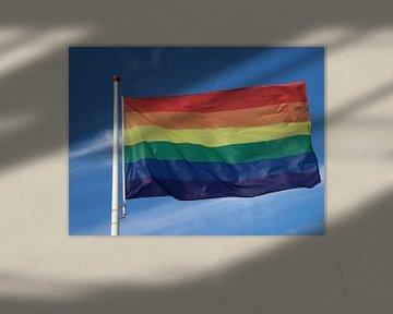 Le drapeau arc-en-ciel flotte avec un ciel bleu et des nuages sur André Muller