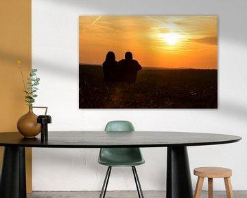 Ein Paar sitzt auf der Wiese und schaut in den Sonnenuntergang