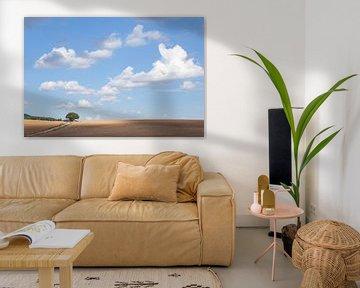 Landschap met boom en blauwe lucht met wolken van Angeline Dobber