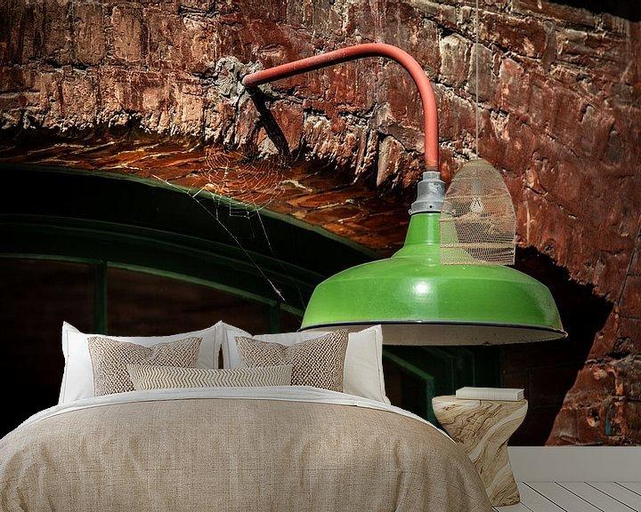 Impression: Lampe en métal vert sur un mur de pierre. sur Jan van Dasler