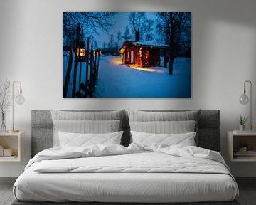 Verlichte houten hut in winterlandschap